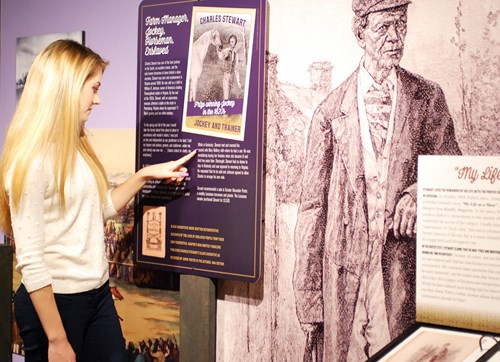 young woman reads museum exhibit near life-size drawing of older gentleman